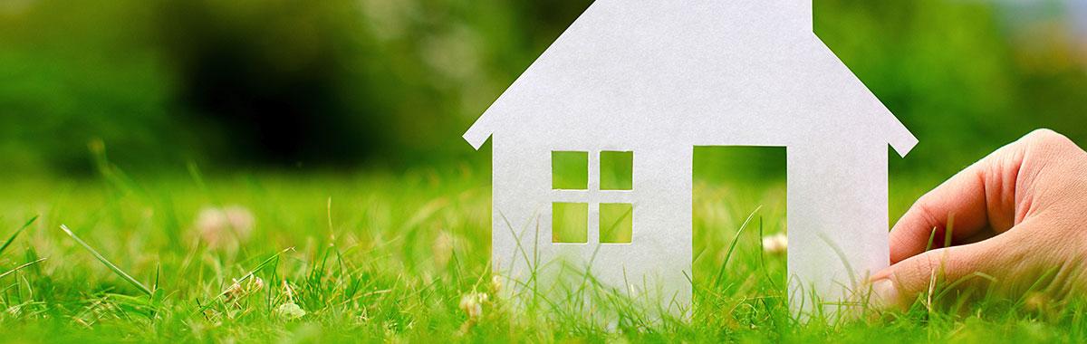 Koristeellinen kuva, jossa käsi nurmikolla pitelemässä paperista tehtyä taloa.