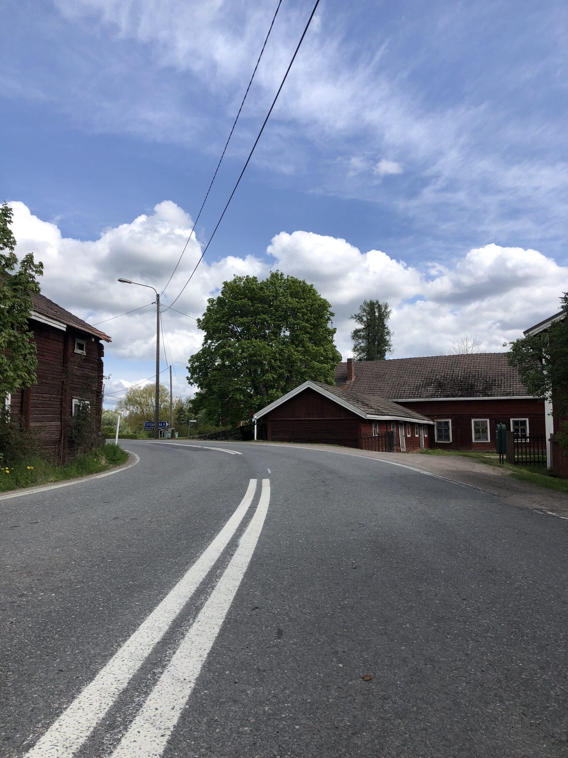 Kuva otettu autotieltä Irjanteen kyläraitilta. Punaisia vanhoja rakennuksia.