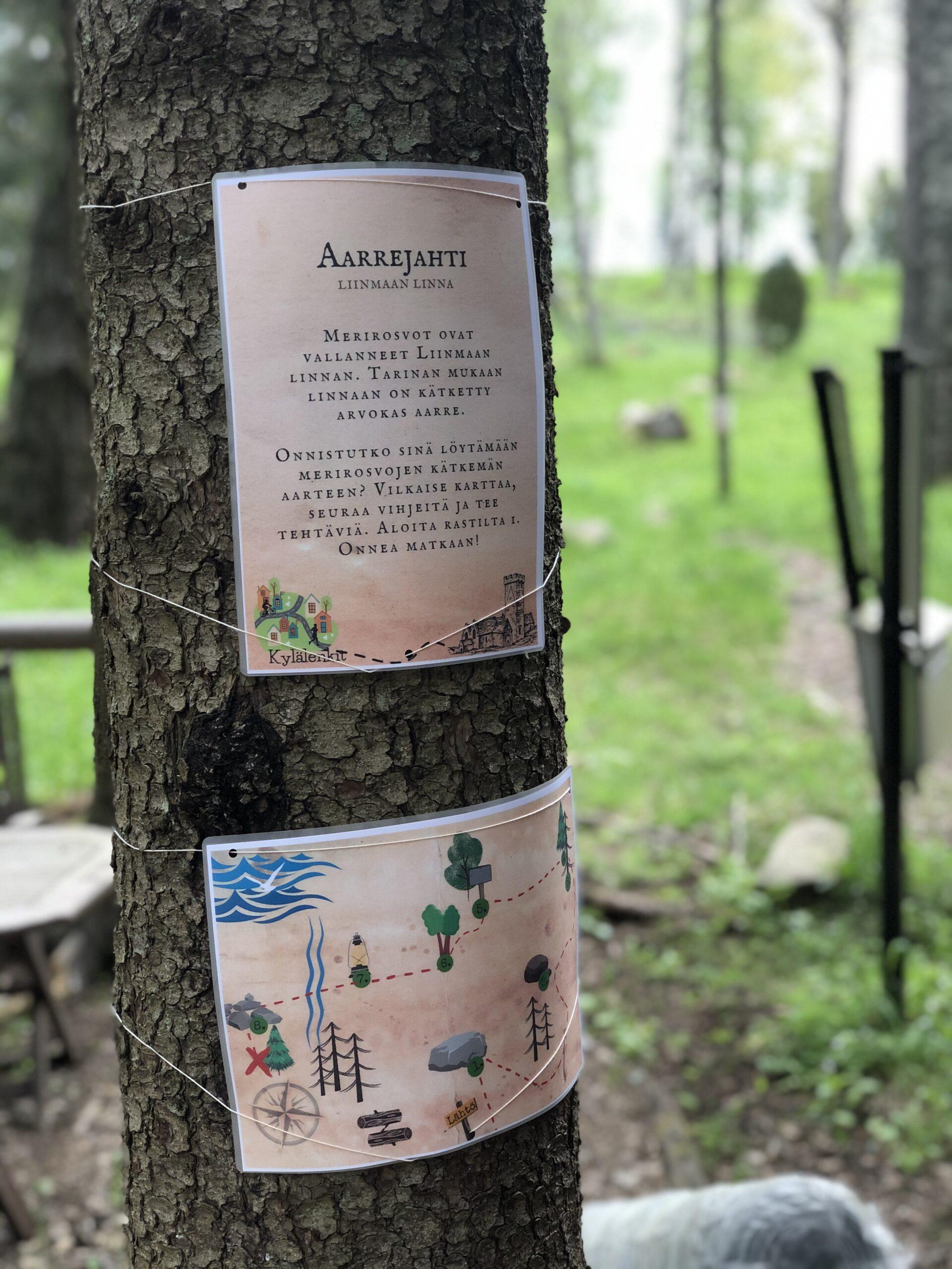 Kuvassa puuhun kiinnitetty kartta ja tekstillä täytetty paperi.